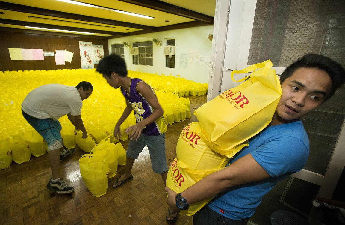 Volunteer Vincent Salazar (right) helps a team with the United Methodist Committee on Relief in Manila as they load bags of relief supplies for survivors of Typhoon Haiyan in the Philippines.