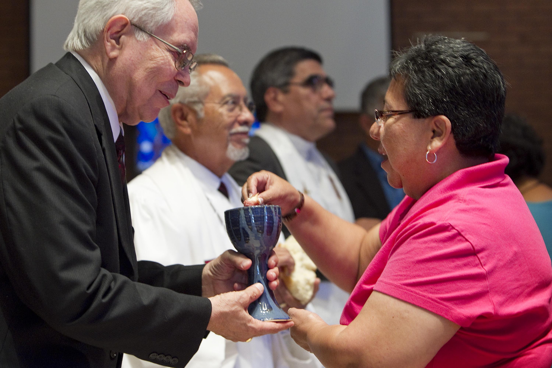 El Rdo. Noé Gonzales (izq.) ofrece la Santa Comunión a Nohemi Ramirez durante el culto de adoración  en El Paso, Texas. Foto: Mike DuBose, Comunicaciones Metodistas Unidas.