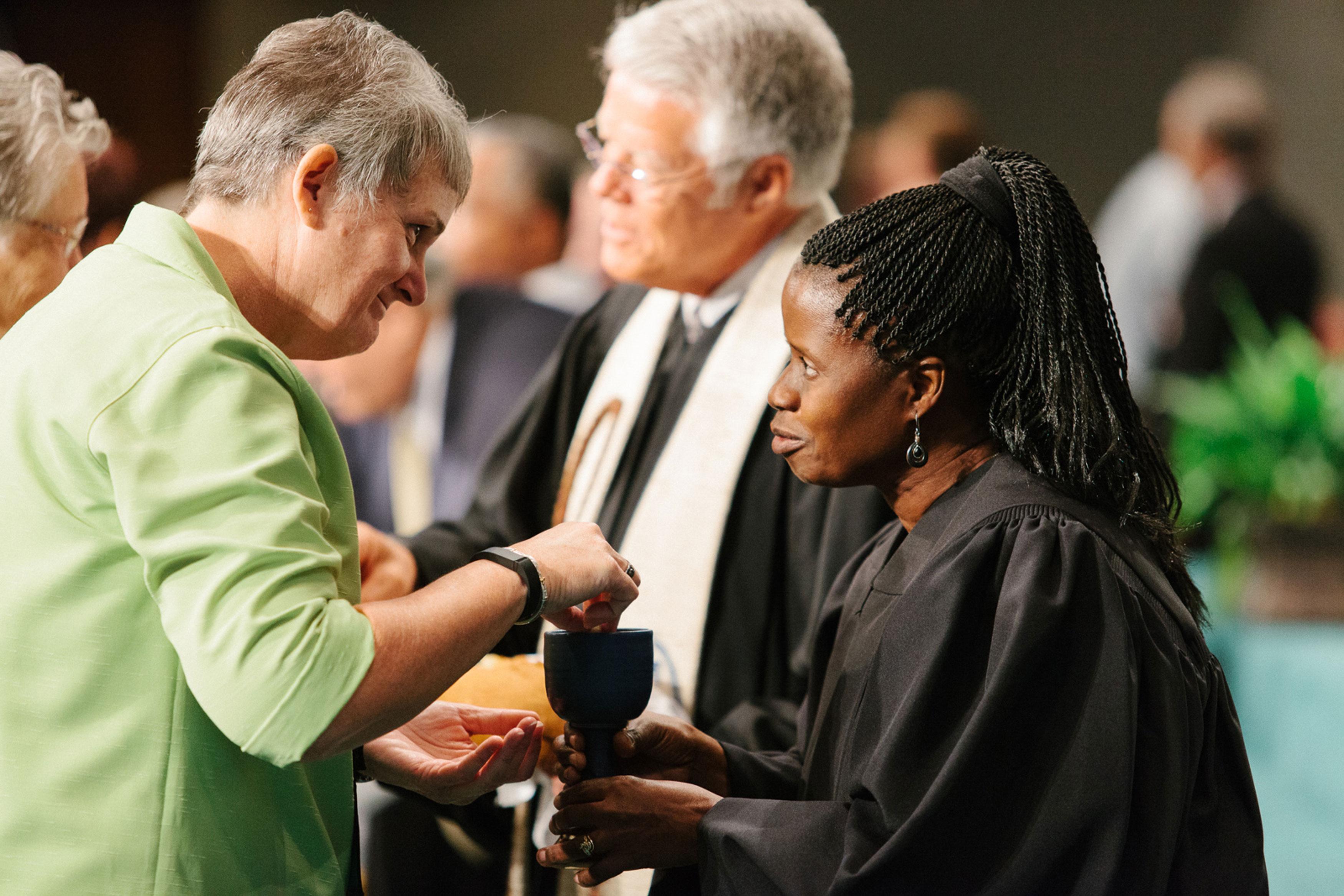 A Revda. Tonya Elmore, pastora da Primeira Igreja Metodista de Enterprise, recebe a ceia da Revda. Virginia Kagoro, pastora da Igreja Metodista Unida Locust Bluff, na conferência de 2015 da região Alabama-West Florida. Foto de Luke Lucas, Alabama-West Florida.