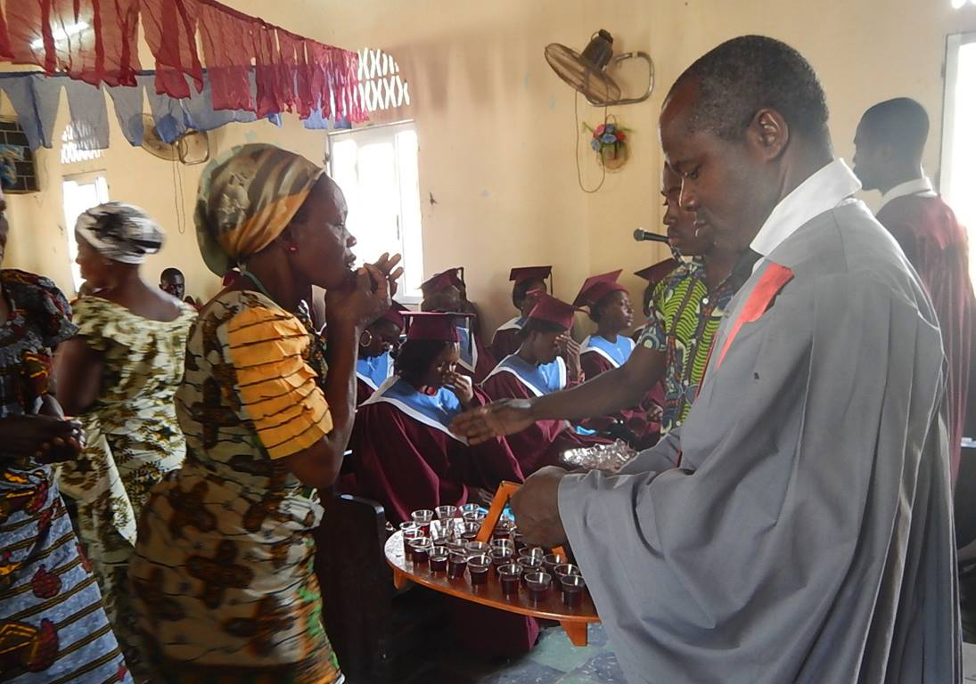 Lay pastor Raphaël Aboua (right) helps serve Holy Communion at Ebenezer Beago United Methodist Church in Abidjan, Côte d'Ivoire. Photo by Isaac Broune, UMNS.