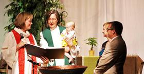 Bishop Elaine J.W. Stanovsky baptizes the daughter of two elders during the 2013 Rocky Mountain Annual Conference. File photo, United Methodist Communications.