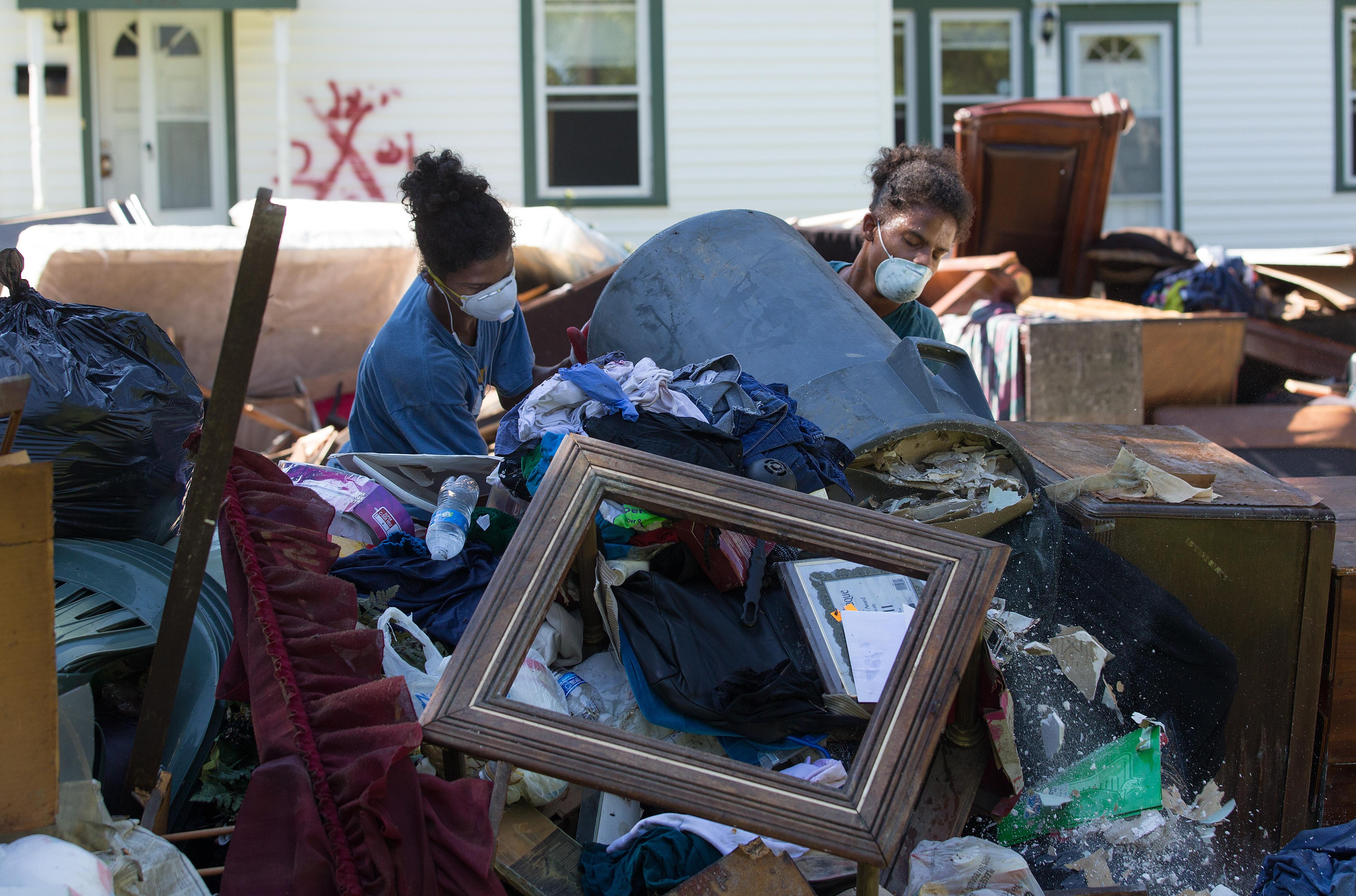 Jeremain (izquierda) y Jeremaih Robinson juntan muebles arruinados  de una casa tremendamente dañada por una inundación en Baton Rouge, La. Estos mellizos de 16 años eran parte del equipo de voluntarios de la Primera Iglesia Metodista de Baton Rouge. Foto por Mike DuBose, UMNS.