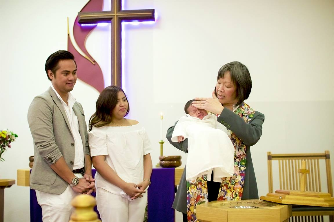 The Rev. Anne Lau Choy baptizes an infant at St. Paul United Methodist Church in Fremont, Calif. Photo by Brian Teodoro.