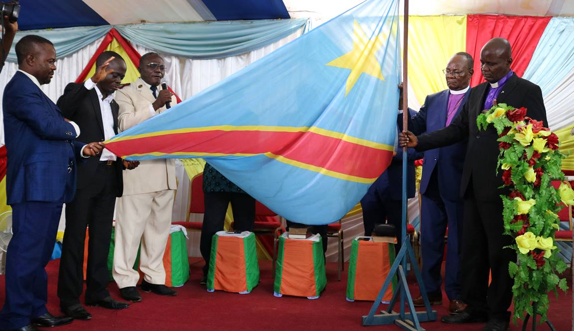 Bishops and leaders of different religious denominations pray while holding the Congolese flag. The Integrity and Electoral Mediation Commission, chaired by United Methodist Bishop Gabriel Yemba Unda (second from right), organized a service to promote peace before, during and after the elections. Photo by Chadrack Londe, UMNS.
