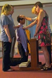 A young man is confirmed by his pastor.