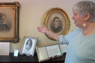 Donna Miller of Historic St. George's United Methodist Church in Philadelphia points out images of Ann and Anna Jarvis at the church. Video image by United Methodist Communications.