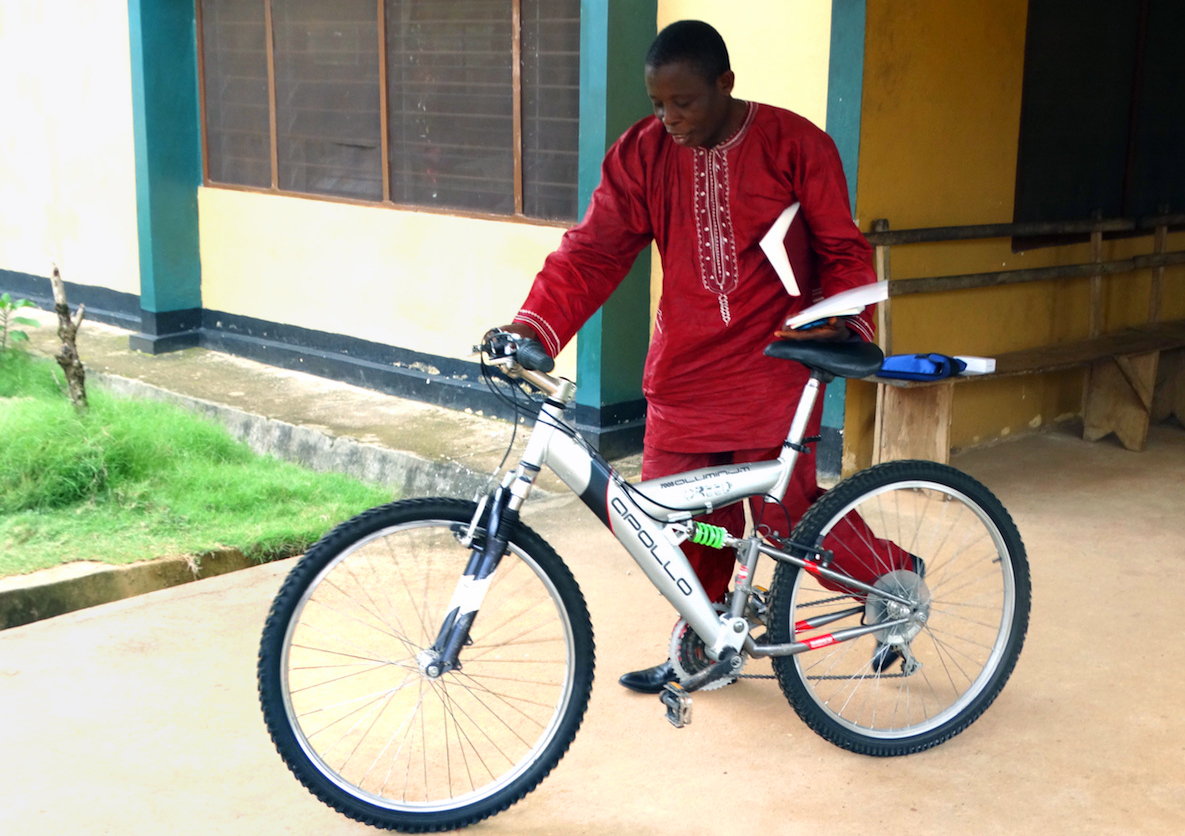 The Rev. Canon James George of the Anglican Church walks away with a new bicycle, a gift to his church after a three-day Bikes and Bibles training session in Bo, Sierra Leone. The program aims to support clergy engaged in rural evangelism by providing them with bicycles, motorcycles and Bibles to work in areas that are difficult to reach. Photo by Phileas Jusu, UMNS.