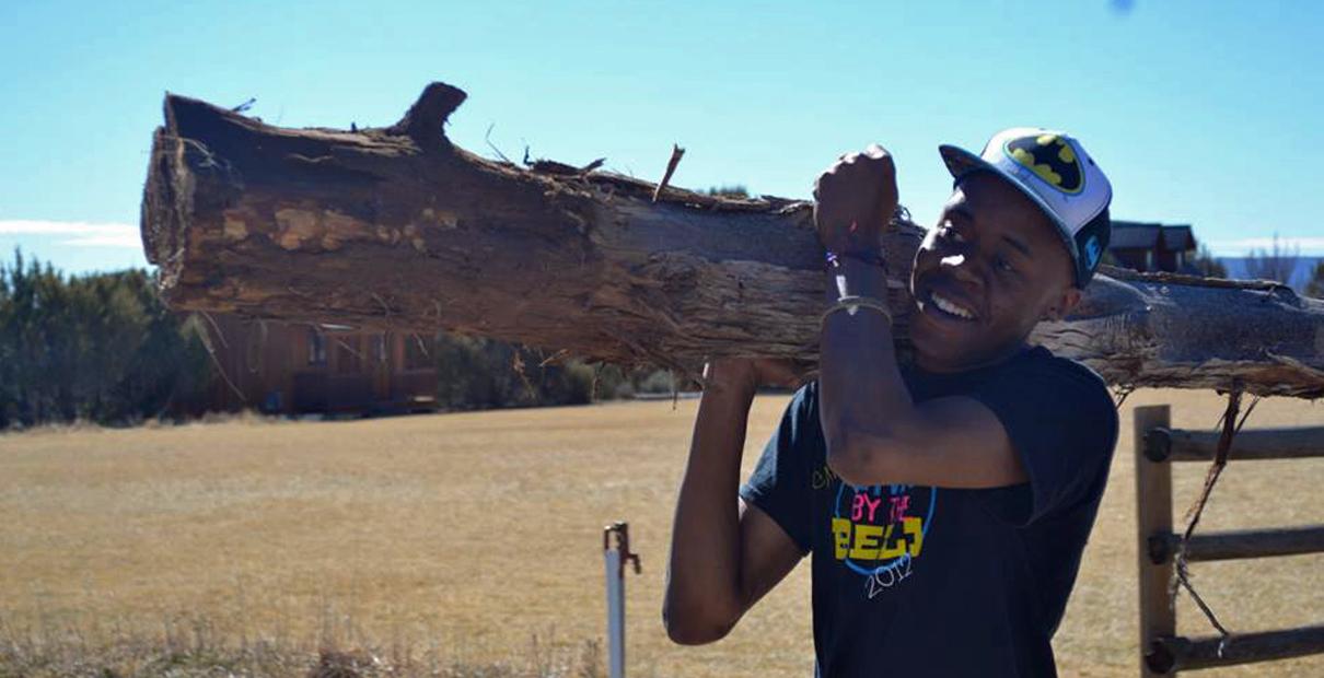 Dakarayi Chabaya, student at Central Methodist University carries a log during one of his mission trips. Photo courtesy of Dakarayi Chabaya.