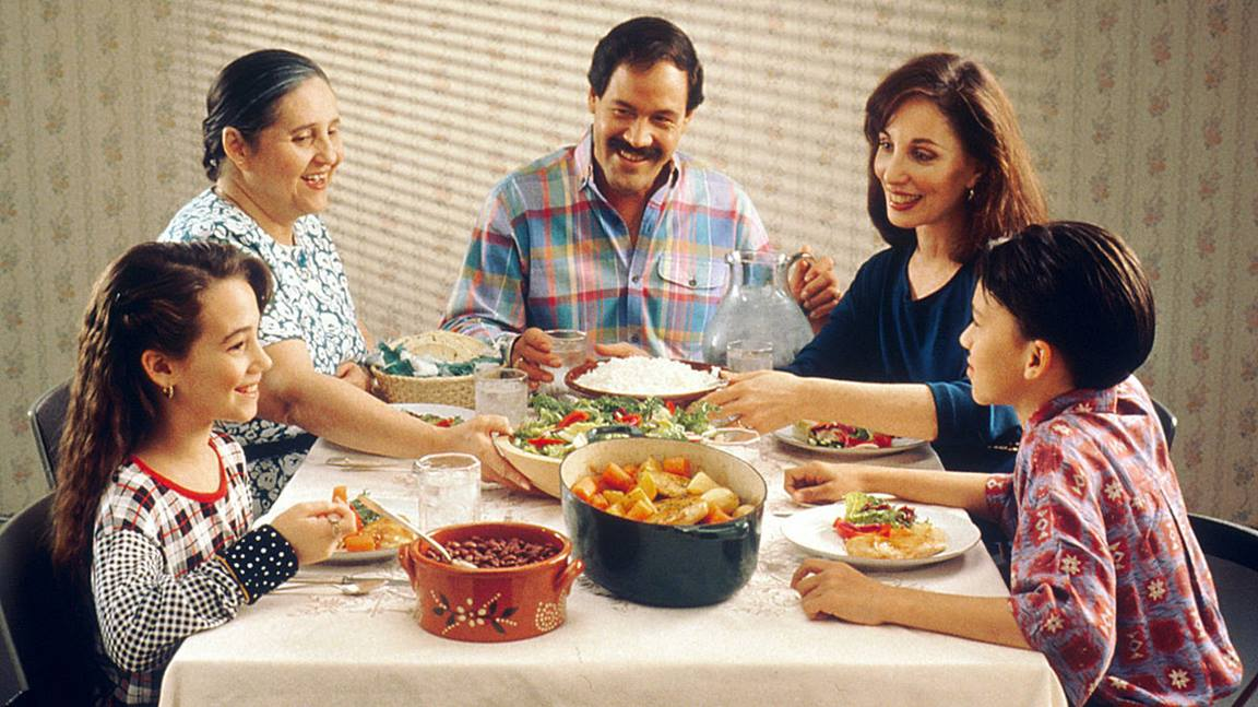 A Hispanic family (male adult, two female adults, female child, and male child) enjoy a meal at the dinner table.