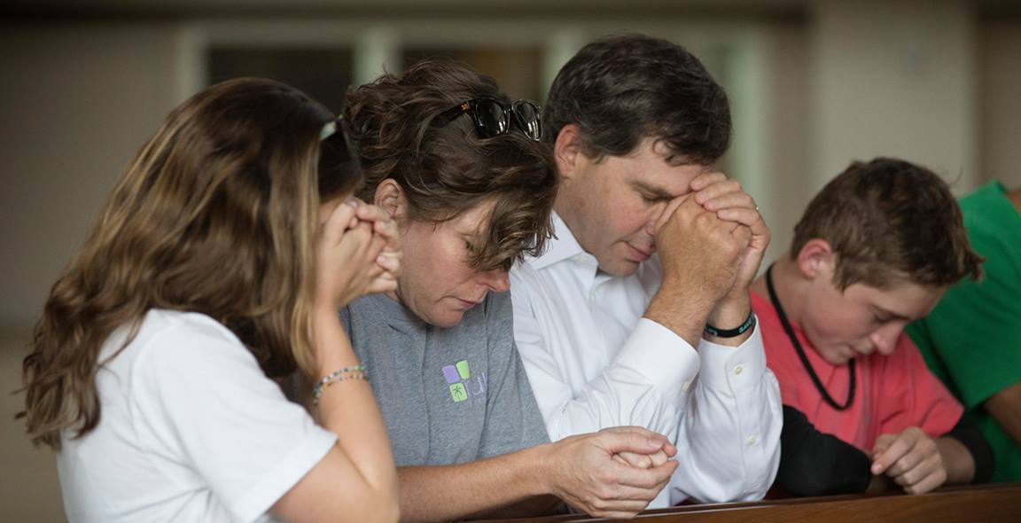 Young adults whose parents shared the importance of their faith are far more likely to continue in church. Members of the Bonn family pray during a 2014 service at Christ United Methodist Church in Franklin, Tenn., to lift up those facing the Ebola crisis in West Africa. Photo by Mike DuBose, United Methodist Communications.