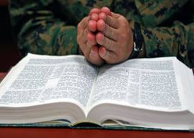Praying hands over a Bible.