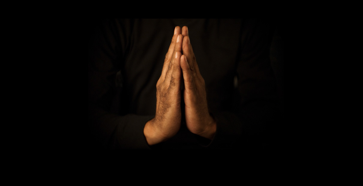 An image of hands in prayer. Photo illustration by Mike DuBose, UMNS.