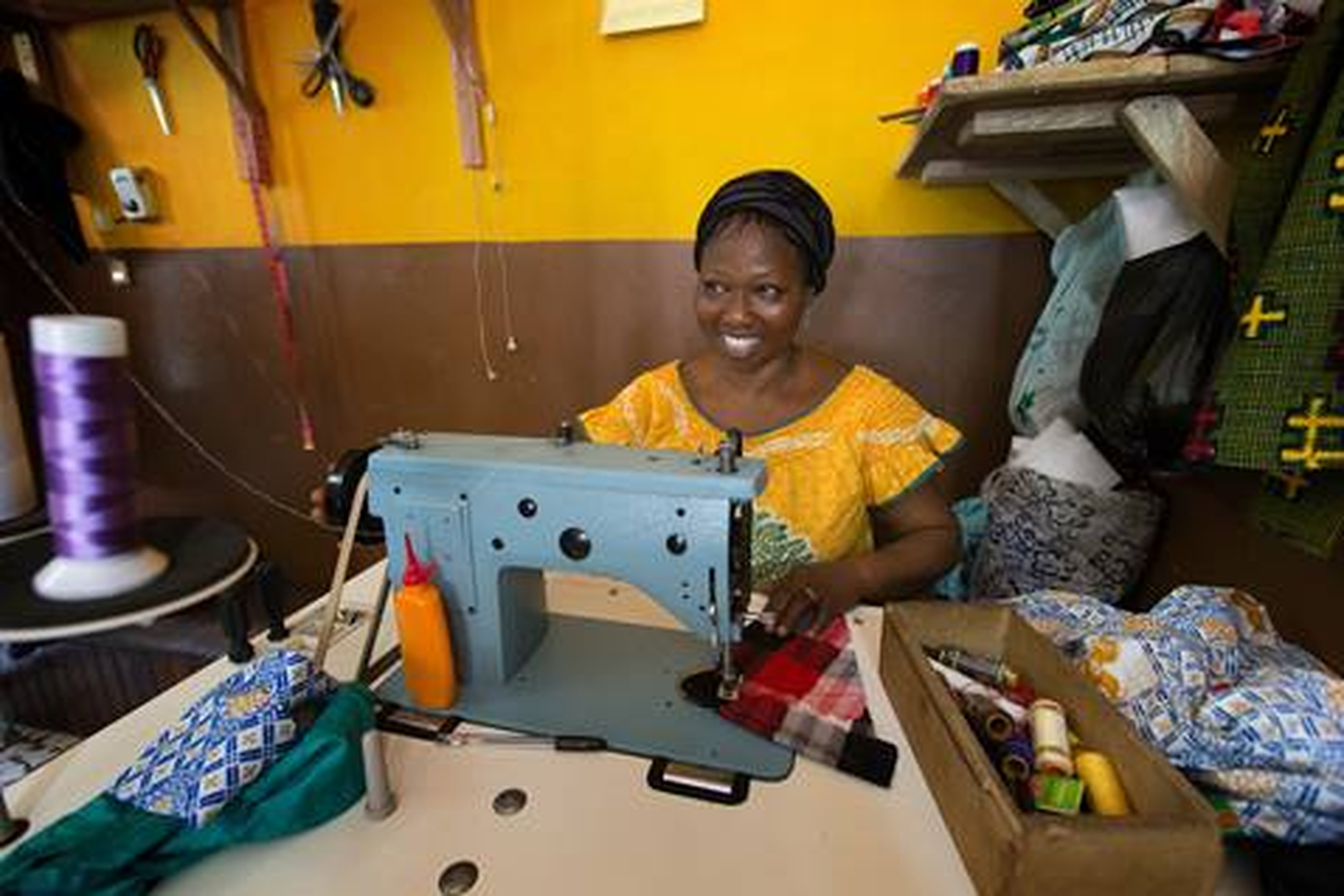 Eugenie Sowan Erse N'Ghessan cose ropa para ganarse la vida y sus siete hijos en Abidjan, Costa de Marfil. Es una de las 48 mujeres que recibió un microcrédito para iniciar su propio negocio en la Conferencia de las Mujeres Metodistas Unidas de Costa de Marfil. Foto de Mike DuBose, Comunicaciones Metodistas Unidas