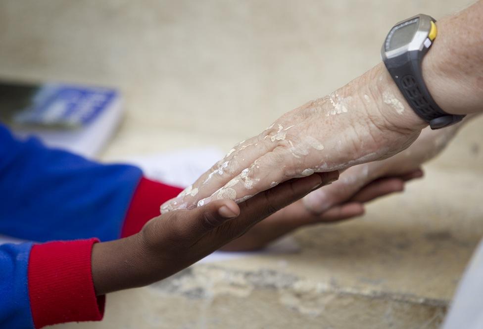 """""""Suas mãos salpicadas de tinta, a voluntária Kathy Ahmad (à direita) joga um jogo com Franckenson Renevil durante um intervalo da reforma do orfanato Methodist Children's Home, em Porto Príncipe, Haiti, em 2010. Foto de Mike DuBose, United Methodist News Service""""."""