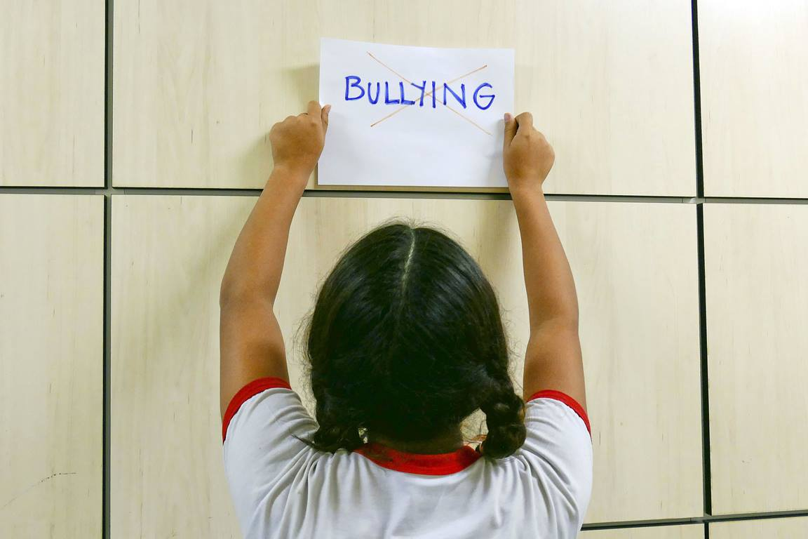 Child holds anti-bullying sign. Photo illustration courtesy of Wikimedia Commons/Senado.