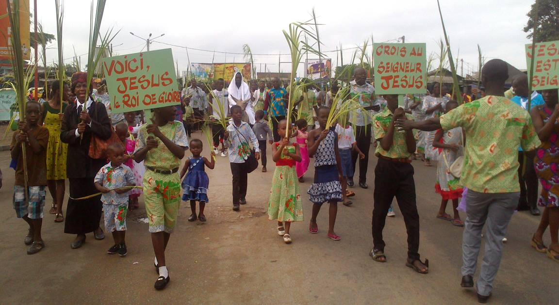 Crowds waving palm branches process through the streets of Port-Bouët, Cote d'Ivoire on Palm Sunday 2015. A man portrays Jesus Christ riding on a donkey. This joyful scene is repeated all over the country by Ivorian United Methodists and Catholics.