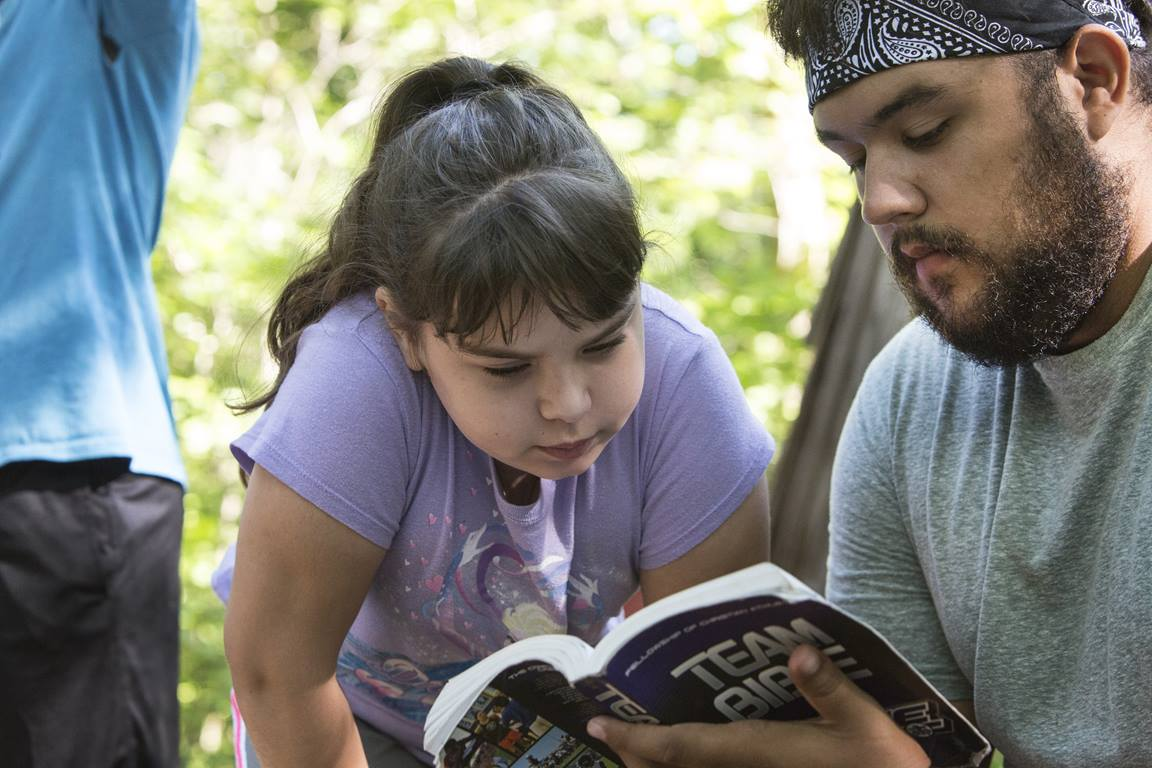 Camper Klaira Hargrove studies the Bible with counselor Emilio Almendarez during morning worship at Cedar Crest Camp in Lyles, Tennessee.