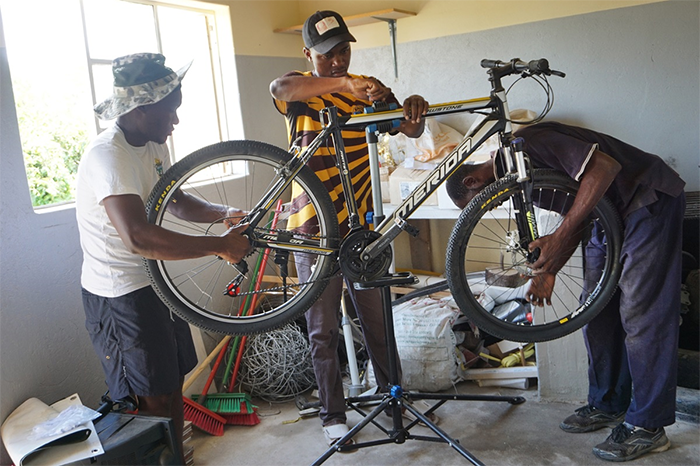 Gedion Mawoneke, Benjamin Dhliwayo and Damion Mutinhiri assemble a bicycle. United Methodist Church's St. John's Circuit in Mutare, Zimbabwe, is helping those in the Deaf community learn skills through the Holy Bike Sales project.