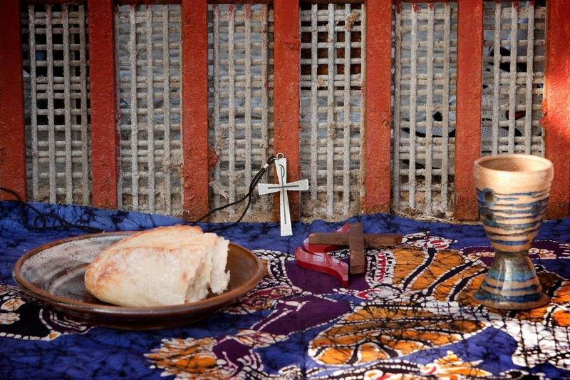 The elements of Holy Communion are laid out against the Mexico side of the border fence between Tijuana and San Diego during a cross-border service at El Faro park in Tijuana, Mexico. Photo by Mike DuBose, UMNS