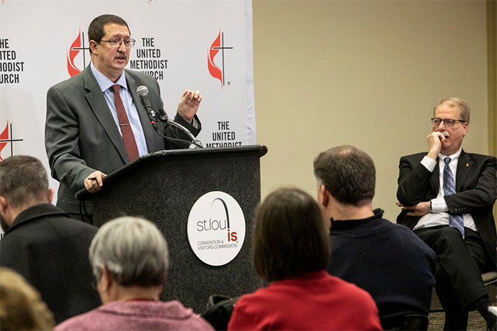 The Rev. Gary W. Graves, secretary of the General Conference, speaks to the press following the conclusion of the special session in St. Louis. To the right is Bishop Kenneth H. Carter.