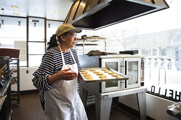 Karen Lamb puts butterscotch oatmeal cookies into the oven Tuesday at Lulu's on N. With the help of paying customers, the restaurant owner offers free meals to those who can't afford one.