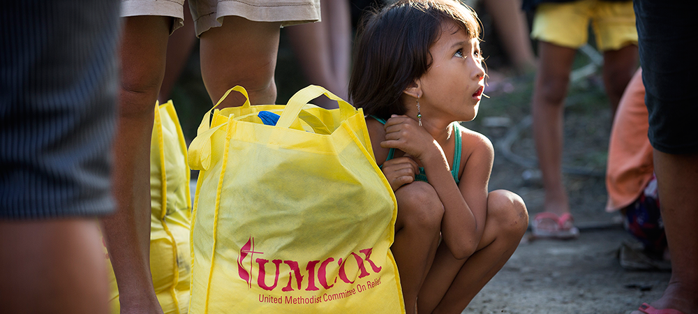 Donna-Grace Orbong, 5, sits with her family's food bag following a distribution by the United Methodist Committee on Relief for survivors of Typhoon Haiyan in Tacloban, Philippines.