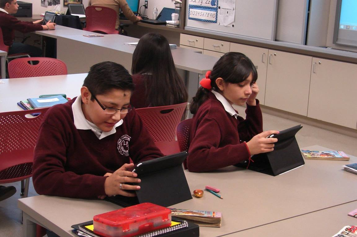 Students work with tablet computers.