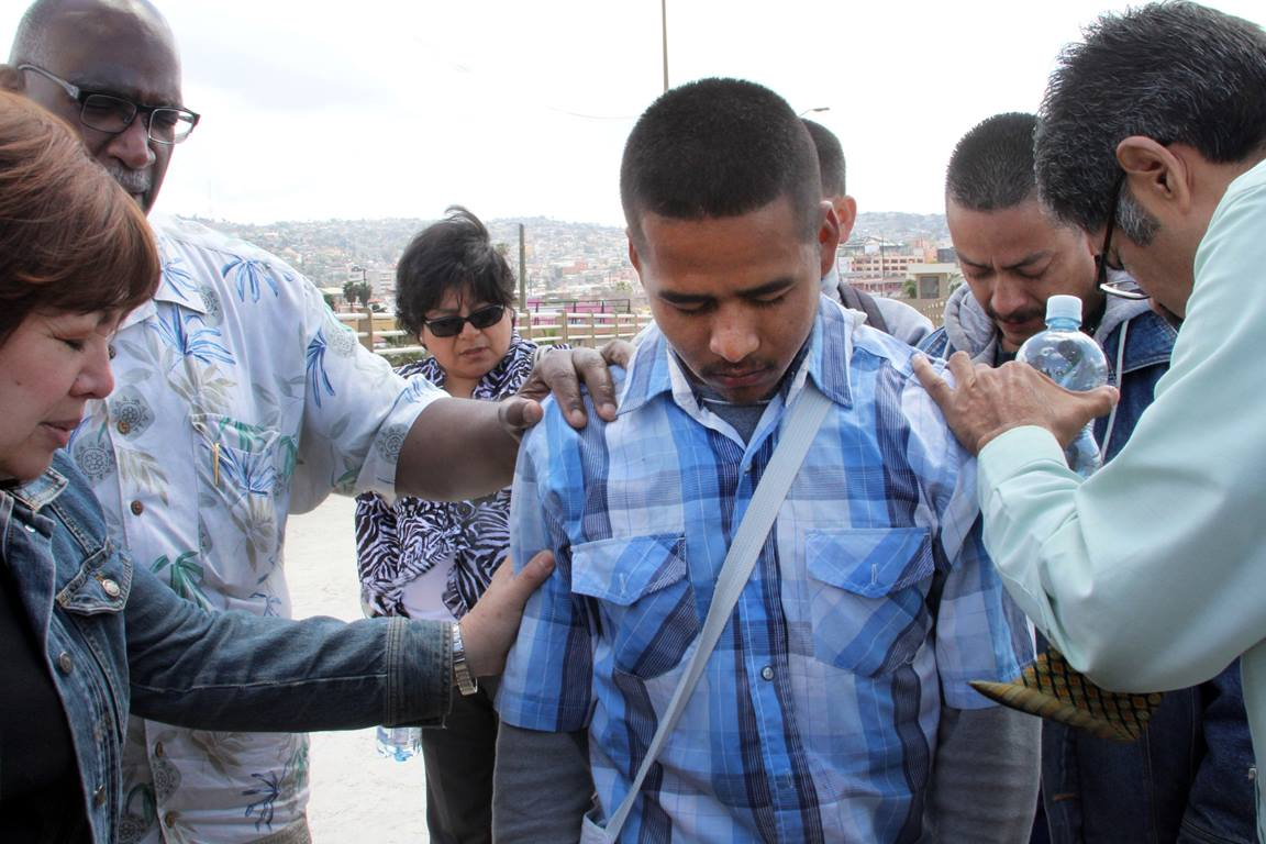 Bishop Minerva Carcaño, Bishop Gregory Palmer and others prayer with a young man, Angelo Mondragon, on the Mexico Bridge. Photo by Kathleen Barry, UMNS