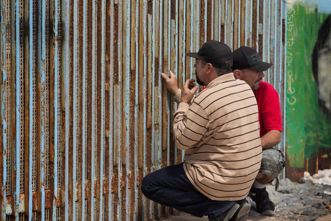 Family members visit through the border fence that separates Mexico from the U.S. at El Faro Park in Tijuana, Mexico.