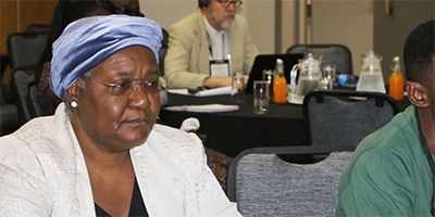 Bishop Joaquina F. Nhanala of Mozambique and agricultural missionary Innocent Afful listen to The United Methodist Church's plans for existing land in Africa during an agricultural summit held Jan. 13-16 in Johannesburg.