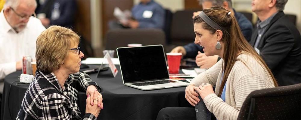 Judi Kenaston, Northeastern Jurisdiction, talks with Michelle Hettman, Southeastern Jurisdiction, during the meeting of the Connectional Table held at United Methodist Discipleship Ministries in Nashville, Tenn., April 2.