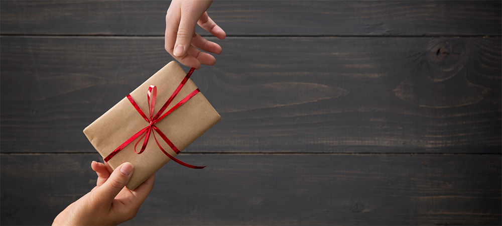 Stock photo of one hand passing a gift to another hand.