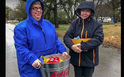 Two Volunteers help pass out snacks to kids during cold and wet weather.