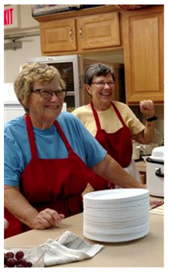 Biscuits, pancakes, or both? Louise Foster and Diane Powell greet guests at the counter during Monday Meals.