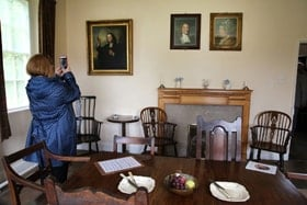 The Wesley family gathered for meals in the dining room of the Old Rectory in Epworth. Portraits of Samuel and Susanna Wesley are mounted above the fireplace, with a portrait of John Wesley to the left. Photo by Kathleen Barry, United Methodist Communications.