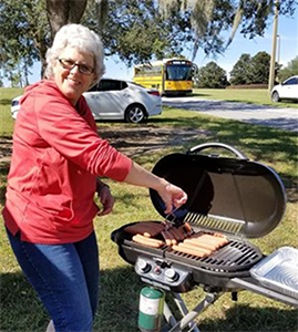 Volunteer of Joining Hands Mission UMC cooks up hotdogs for community event. Courtesy photo.