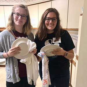 Emma Allen, (left) and friend drying dishes.