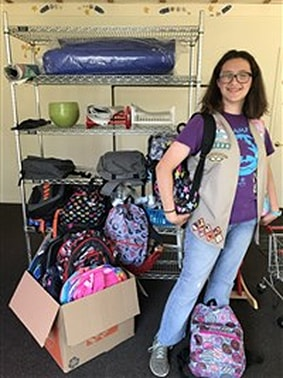 Elena poses with backpacks full of supplies.