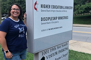 Brittani Fletcher stands next to the General Board of Higher Education and Ministry Agency's sign in Nashville, TN.