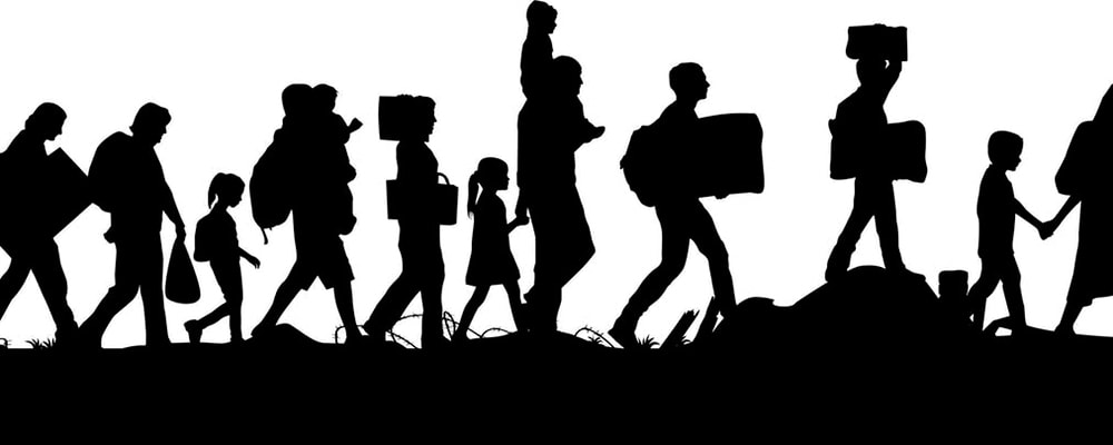 Silhouette of imigrants walking to freedom. Stock photo.