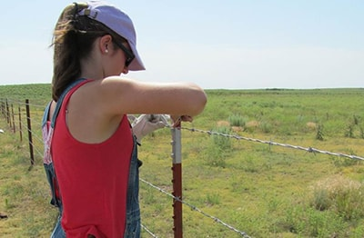 Summer Lackey mends a fence on family farm. Courtesy photo.