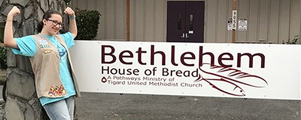 Elena Villarreal stands in front of sign at Bethlehem House of Bread. Courtesy photo.