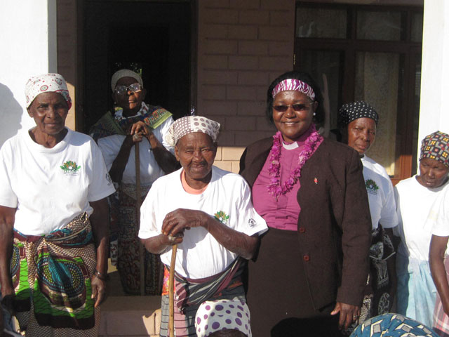 United Methodist Bishop Joaquina Nhanala (center) celebrates the completion of three permanent shelters with widows at the Hanhane Shelter. Photo by Naftal Massela.