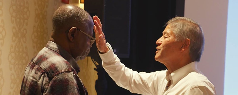 Bishop Grant Hagiya, at right, blesses retired Bishop David Yemba as part of the bishops' renewal of their baptism vows at the conclusion of the spring Council of Bishops meeting. Hagiya leads the California-Pacific Conference and Yemba serves in the Democratic Republic of Congo. Photo by Heather Hahn, UMNS.