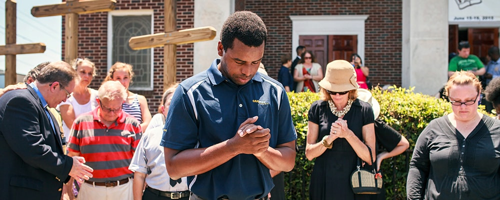 Robert Griggs (center) prays with others outside Morris Brown African Methodist Episcopal Church in Charleston, S.C. United Methodists joined AME members in prayers following the deadly shooting at Emanuel AME Church in Charleston.