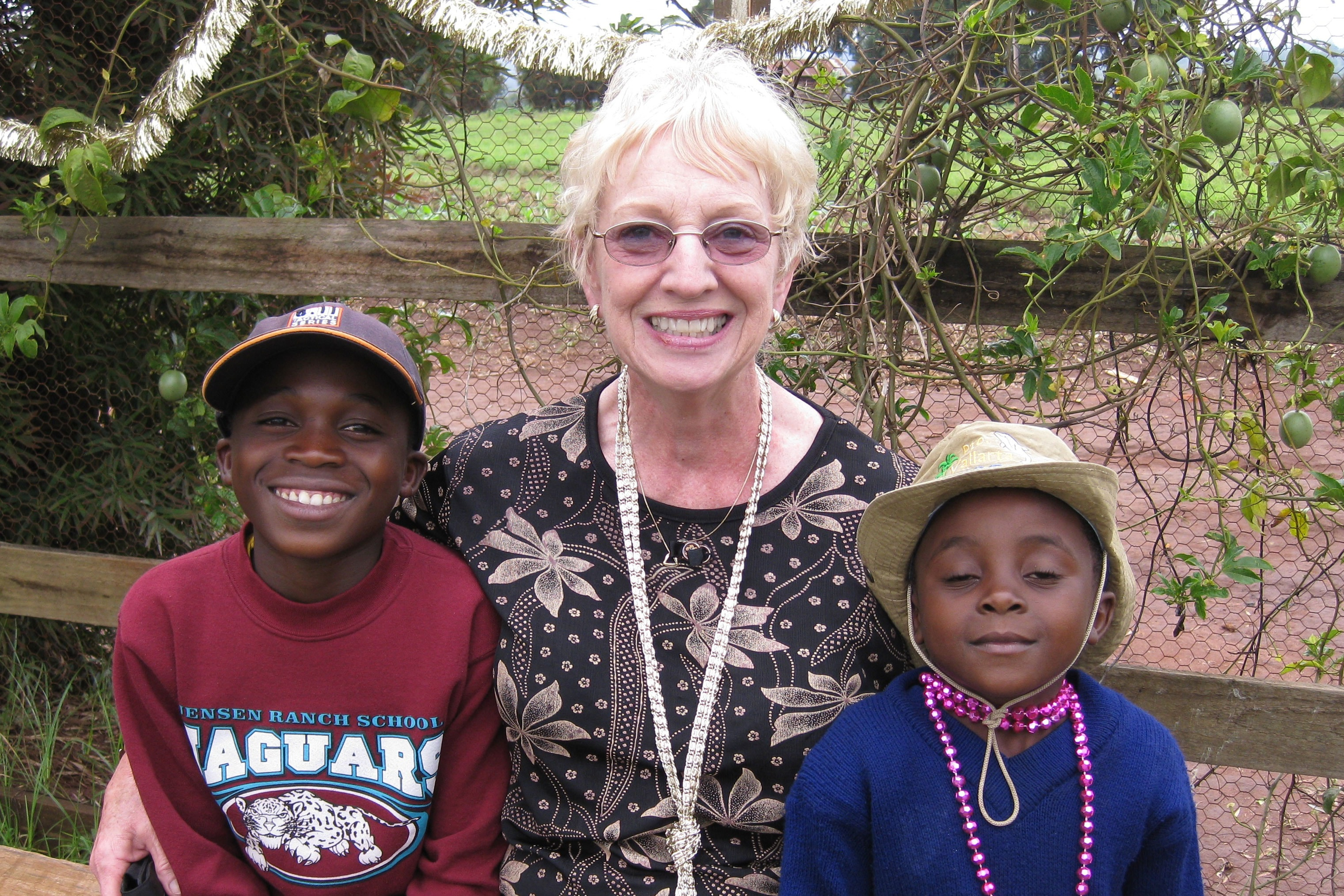 Kay 'Bibi Kay' Oursler sits with two children who live at Sunrise Children's Home in Tanzania, the orphanage Oursler founded. Photo courtesy of Kay Oursler.