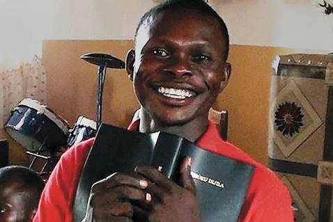 This smile shows the happiness felt by a man in the Democratic Republic of the Congo who is holding a Bible in his own language. Photo courtesy Asbury United Methodist Church.
