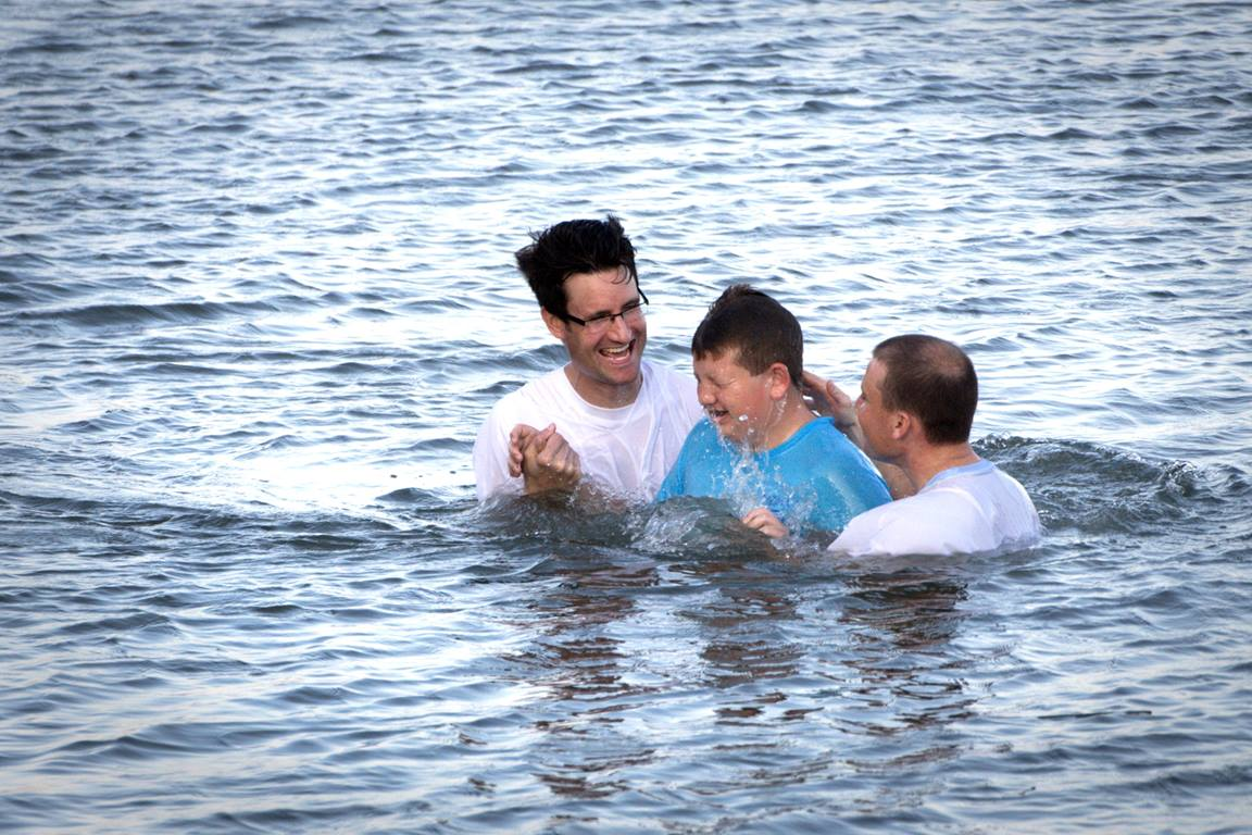 Marshall Greene (center) is baptized during the Annual Inlet Baptism in Murrells Inlet off the Belin Memorial United Methodist Church's seawall. Holding him is (left) Austin Bond, director of youth ministries and (right) Walter Cantwell, associate pastor. Photo by Benjamin Coy.