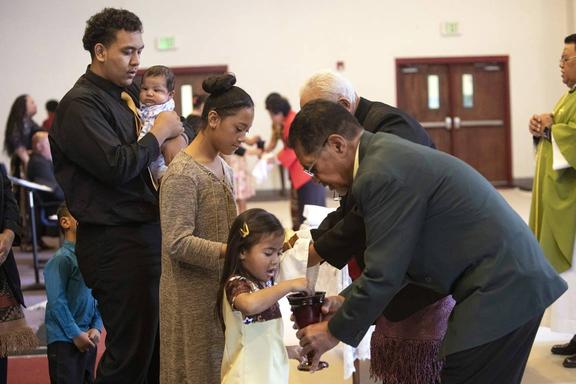 Young adult, Sekope Fainu (left), waits to receive Communion during worship at Tongan United Methodist Church in West Valley City, Utah. Photo by Kathleen Barry, UM News.