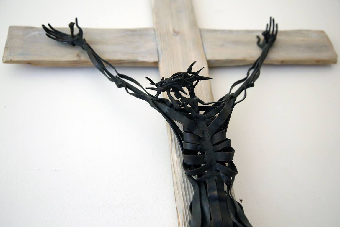 An abstract metal crucifix hangs on the wall outside the chapel at Sarum College in Salisbury, England. Photo by Kathleen Barry, United Methodist Communications.